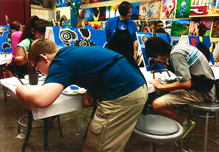 two students leaning over their work table painting
